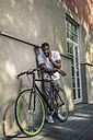 Portrait of young man with bicycle telephoning with smartphone - RIBF000116