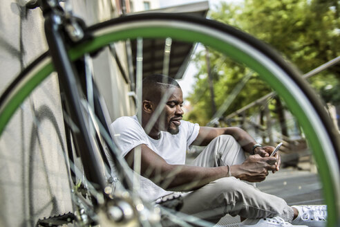 Portrait of young man sitting behind bicycle telephoning with smartphone - RIBF000117