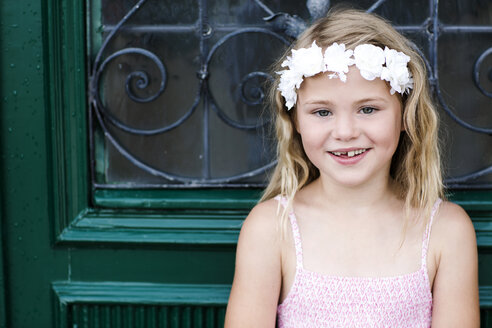 Portrait of smiling girl with tooth gap wearing floral wreath - GDF000766