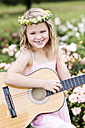 Portrait of smiling little girl with guitar wearing floral wreath - GDF000777