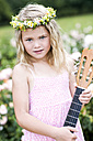 Portrait of little girl with guitar wearing floral wreath - GDF000768