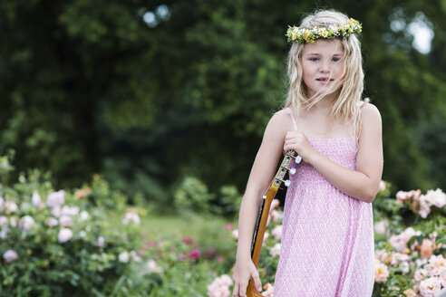 Portrait of little girl with guitar wearing floral wreath - GDF000770