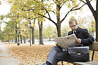 Businessman on park bench reading newspaper - WESTF021382