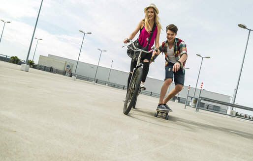 Happy young couple with bicycle and skateboard - UUF004865