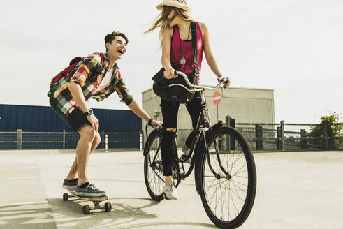 Happy young couple with bicycle and skateboard - UUF004866