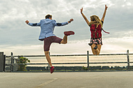 Enthusiastic young couple jumping on parking level - UUF004911