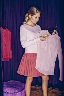 Young woman in fitting room with a blouse - CHAF000530