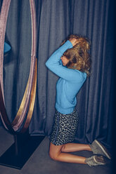 Young woman kneeling in a fitting room - CHAF000539