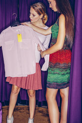 Two young women in fitting room with a blouse - CHAF000544