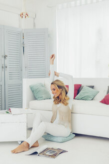 Smiling blond woman relaxing on the floor at her living room - CHAF000944