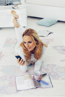 Portrait of blond woman lying on floor at her living room looking at smartphone - CHAF000946
