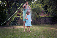Two sisters with garden hose in the garden - LVF003674