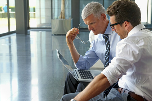 Two businessmen working on laptop in office lobby - CHAF000371