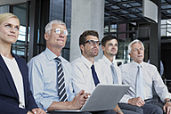 Group of businesspeople sitting in a row looking up - CHAF000396