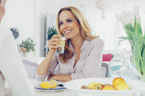 Portrait of smiling blond woman sitting at dining table communicating with her female friend - CHAF000403