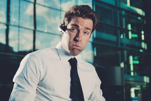 Businessman wearing bluetooth wireless device outside office building - CHAF000412