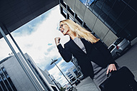 Businesswoman with clenched fist outside office building - CHAF000416