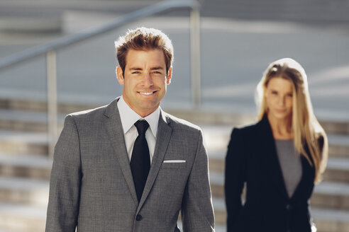 Smiling businessman with businesswoman in background - CHAF000425