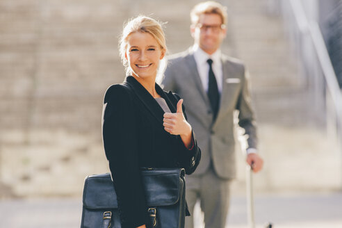 Optimistic businesswoman with businessman in background - CHAF000434