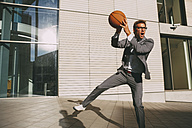 Businessman playing basketball outdoors - CHAF000438
