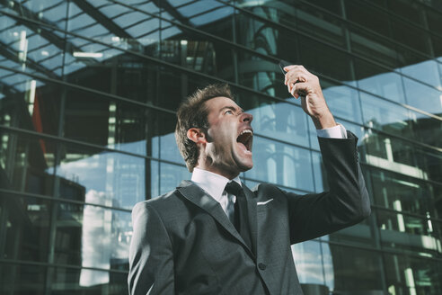 Angry businessman screaming at cell phone outside office building - CHAF000556
