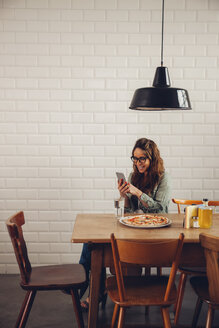 Young woman eating pizza in restaurant, using mobile phone - CHAF001280