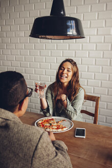 Young couple eating pizza in restaurant - CHAF001292