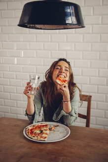 Young woman eating pizza in restaurant - CHAF001296