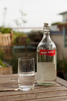 Water glass and bottle on table in garden - HCF000125
