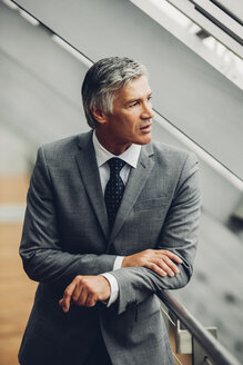 Mature businessman standing by railing looking away - CHAF000488