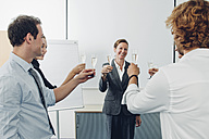 Group of business people raising a toast with champagne at office - CHAF001327