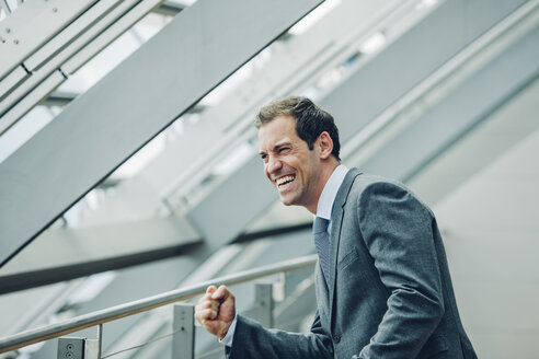 Businessman in office building cheering, celebrating success - CHAF000529