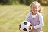 Portrait of smiling little girl with soccer ball on a meadow - STKF001319