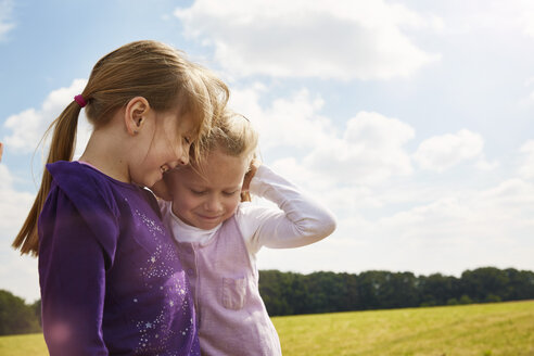 Two little girls playing on a meadow - STKF001325