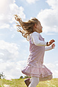 Little girl jumping on a meadow trying to catch soap bubbles - STKF001337