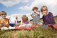 Children sitting on a blanket eating sweets - STKF001346