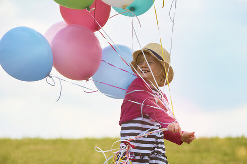 Little girl with balloons on a meadow - STKF001349