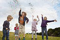Five little children throwing confetti on a meadow - STKF001355