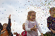 Four little children throwing confetti on a meadow - STKF001358