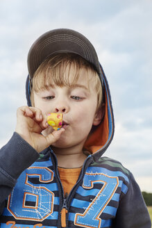 Portrait of little boy with party blowout - STKF001361