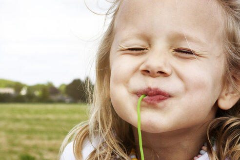 Portrait of happy little girl eating sweets - STKF001367