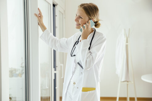 Smiling female doctor talking on cell phone - MFF001822