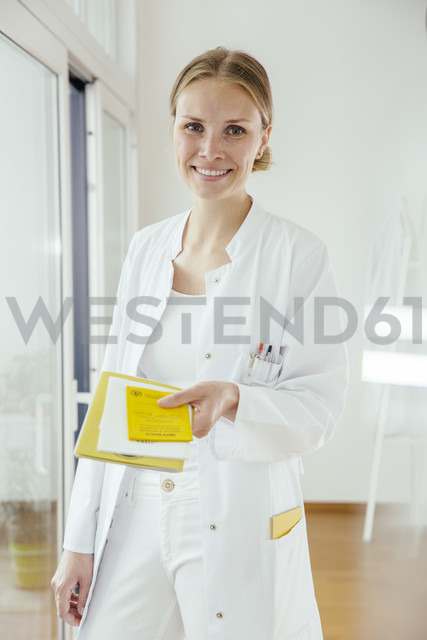 Portrait of smiling female doctor handing over medical documents - MFF001831