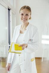Portrait of smiling female doctor handing over medical documents - MFF001831