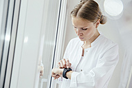 Female doctor looking on her smart watch - MFF001838