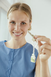 Smiling young woman presenting a house key - MFF001846