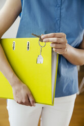 Woman holding a folder and house key - MFF001847