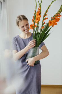 Woman holding a large vase with Gladiola - MFF001855