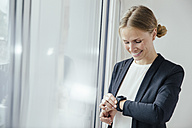 Smiling young businesswoman checking her smart watch - MFF001853