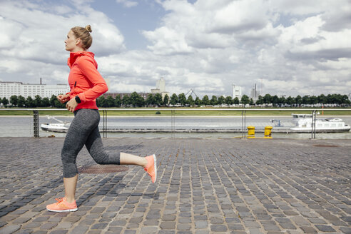 Germany, Cologne, young woman jogging at River Rhine - MFF001862